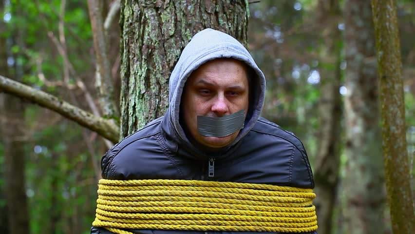 Связанный мужчина в лесу